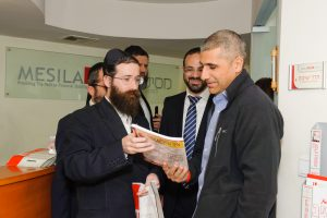 Rabbi Mernstein showing Mesila material to Amir Levy, director of Budgets Department, Ministry of Finance